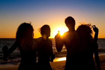 shining through: Persone (due coppie) sulla spiaggia facendo una festa, bere e avere un sacco di divertimento nel tramonto (solo silhouette di persone da vedere, persone che hanno le bottiglie nelle loro mani con il sole che splende attraverso)
