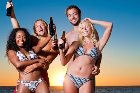 Gruppe von vier Freunden - M�nner und Frauen - stehend mit Getr�nke am Strand gegen die untergehende Sonne �ber dem Ozean