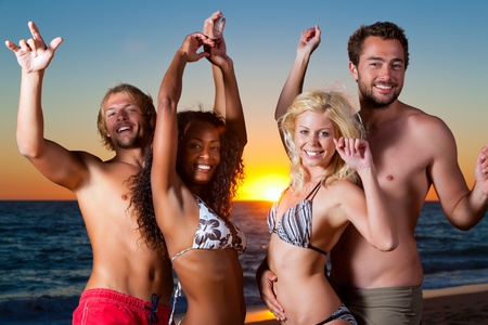 bailando salsa: Personas (dos parejas) en la playa con un partido y con un montón de diversión en la puesta de sol