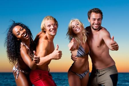 Personen (zwei Paare) am Strand eine Partei und eine Menge Spa� in den Sonnenuntergang