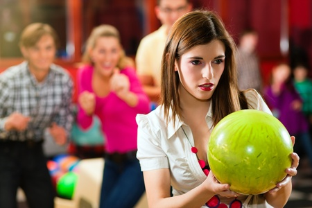 bowling: Group of four friends in a bowling alley having fun, three of them cheering the one girl in charge to throw the bowling ball