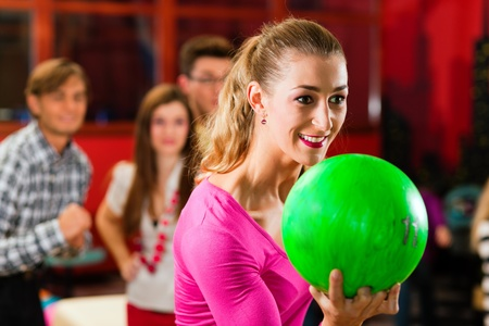 bowling ball: Group of four friends in a bowling alley having fun, three of them cheering the one girl in charge to throw the bowling ball