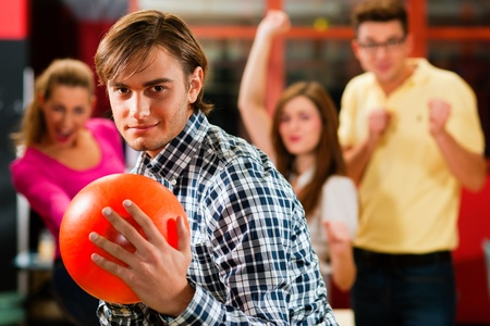 bowling alley: Group of four friends in a bowling alley having fun, three of them cheering the one in charge to throw the bowling ball