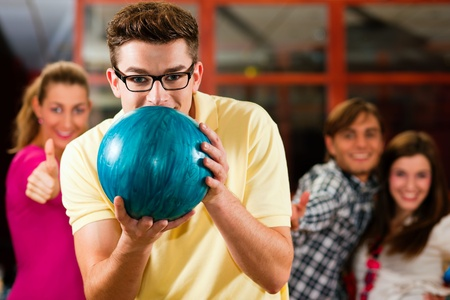 bowling pin: Group of four friends in a bowling alley having fun, three of them cheering the one in charge to throw the bowling ball
