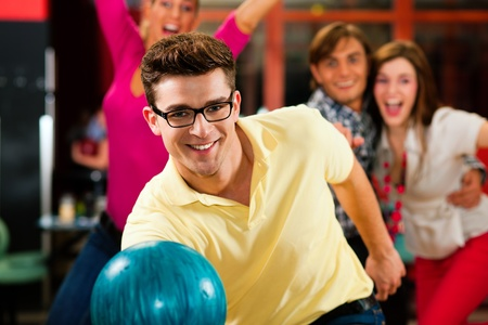 bowling: Group of four friends in a bowling alley having fun, three of them cheering the one in charge to throw the bowling ball