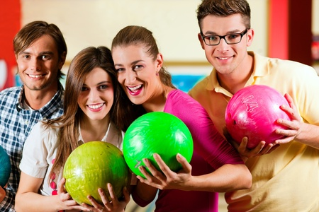 boliche: Group of four friends in a bowling alley having fun, holding their bowling balls