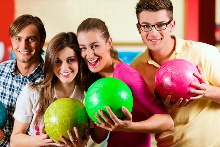 bolos: Grupo de cuatro amigos en una bolera divirtiéndose, sosteniendo sus bolas de bowling  Foto de archivo