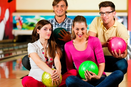 Group of four friends in a bowling alley having fun, holding their bowling balls  photo