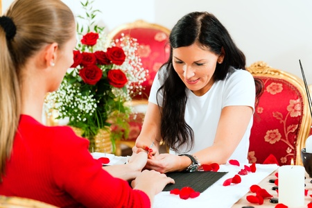 manicurist: Woman in a nail salon receiving a manicure by a beautician, lots of roses in the background Stock Photo