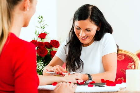 salon background: Woman in a nail salon receiving a manicure by a beautician, lots of roses in the background Stock Photo