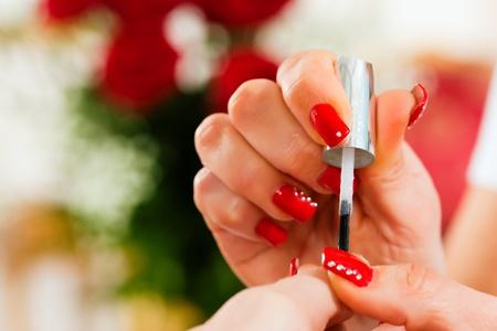 salon de belleza: Mujer en un salón de belleza recibe una manicura por una esteticista, un montón de rosas en el fondo Foto de archivo