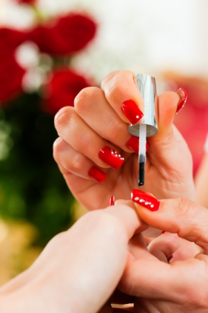 Woman in a nail salon receiving a manicure by a beautician, lots of roses in the background Stock Photo - 10041030