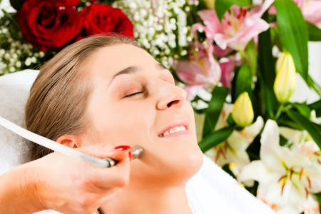 Woman receiving beauty treatment in a Day Spa; lots of flowers in the background
