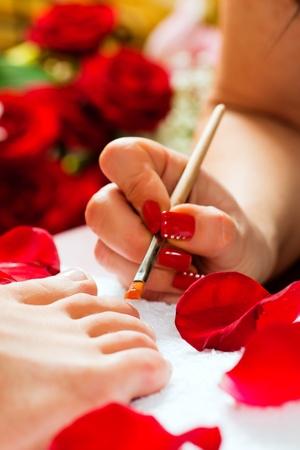 pedicura: Mujer receptora pedicura en un Spa de d�a; montones de flores en el fondo   Foto de archivo