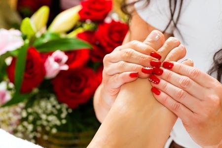 pedicura: Mujer recibiendo masajes de pies con masaje en un Spa de d�a; montones de flores en el fondo