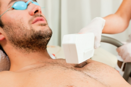waxing: Mann receiving waxing in a Day Spa; for relaxation he wears specs