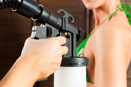 Beautician (only hands to be seen) with airbrush-pistol and client in a cosmetic studio doing bronzing   Stock Photo