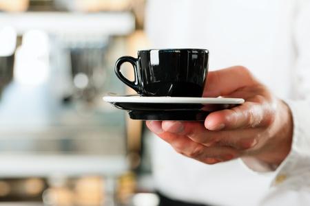 tazas de cafe: Cafetería - barista presenta café o capuchino; primer plano en taza