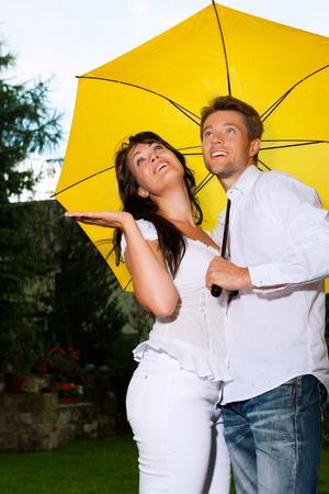 UOMO pioggia: Coppia felice sotto la pioggia d'estate con un ombrello giallo
