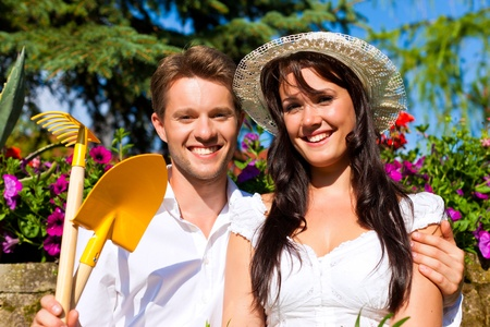 Happy couple gardening in summer with tools; she is wearing a hat photo