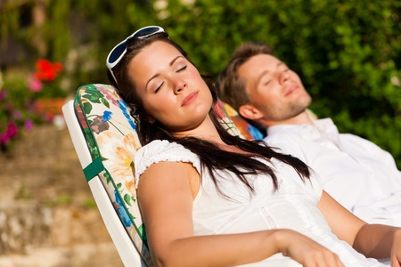 skin cancer: Happy couple - a man and a woman - resting in a deck chair in summer