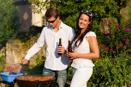 beer garden: Couple - man and woman - doing the barbeque together in their garden in summer Stock Photo