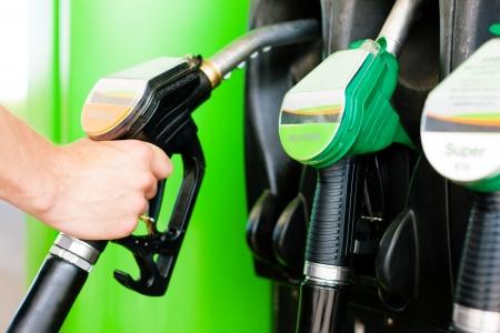 bomba de gasolina: Repostar el coche en una estación de gas; hombre teniendo el grifo