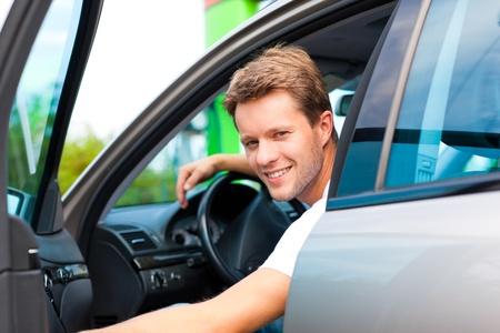 Man in his car stops at petrol station photo