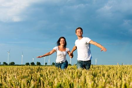 Happy couple running over grainfield in summer hand in hand Stock Photo - 10041183