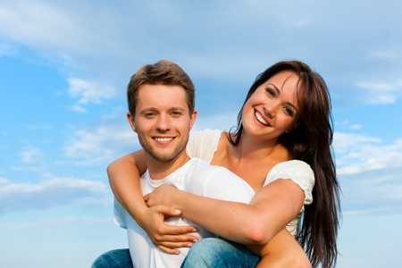 Happy couple under a blue sky; he is carrying her piggyback Stock Photo - 10041185