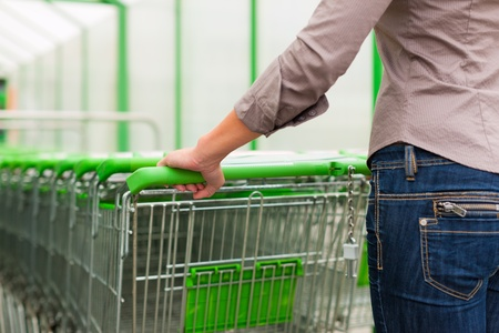 shopping cart: Woman – only torso to be seen - in a supermarket gets a shopping cart for the groceries Stock Photo