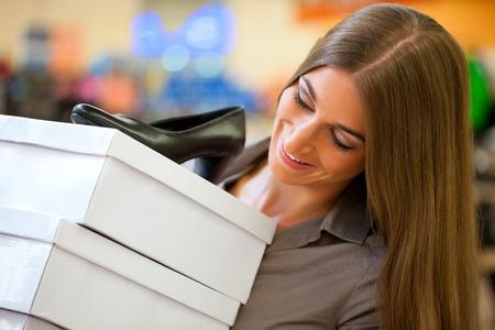 comprando zapatos: Mujer feliz comprando zapatos en la tienda; ella est� comprando bombas Foto de archivo