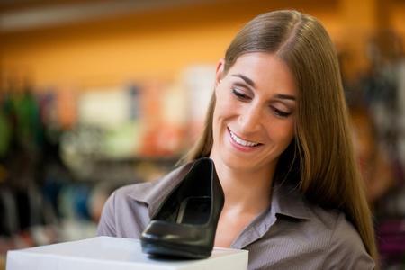 comprando zapatos: Mujer feliz comprando zapatos en la tienda; ella está comprando bombas Foto de archivo