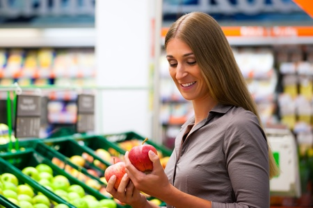 Woman in a supermarket at the shelf for fruits shopping for groceries, she is checking out the apples photo