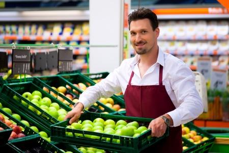 tiendas de comida: Hombre en supermercados como asistente de tienda; trae algunos cuadros con manzanas Foto de archivo