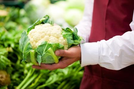 coliflor: Hombre: manos sólo para verse - en supermercados como asistente de tienda; está llevando a cabo una coliflor
