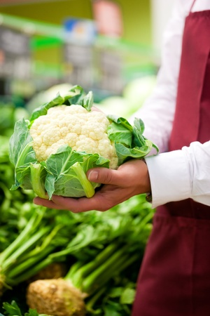 food inspection: Man – only hands to be seen - in supermarket as shop assistant; he is carrying a cauliflower