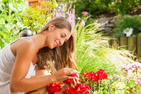 Gardening in summer - happy woman with flowers and hat in her garden Stock Photo