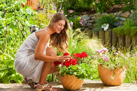 woman gardening: Gardening in summer - happy woman with flowers and hat in her garden Stock Photo