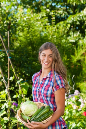 Gardening in summer – happy woman with freshly harvested vegetables photo