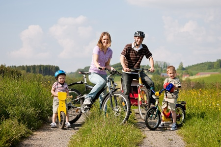 Family with two children having a weekend excursion on their bikes on a summer day in beautiful landscape, for safety and protection they are wearing helmets
