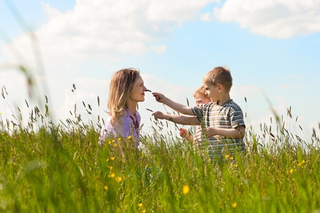 Little boy and his mother blowing dandelion seed for a wish on a meadow outdoors in summer  photo