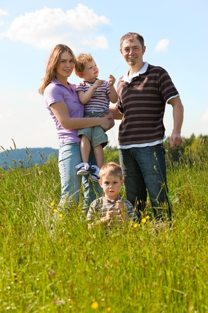 viewer: Very happy family with two kids sitting in a  meadow in the summer sun in front of a forest and hills, they are nearly hidden by the high grass, on boy is running towards the viewer  Stock Photo