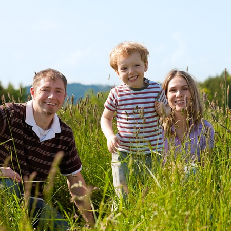 Very happy family with two kids sitting in a  meadow in the summer sun in front of a forest and hills, they are nearly hidden by the high grass, on boy is running towards the viewer  photo