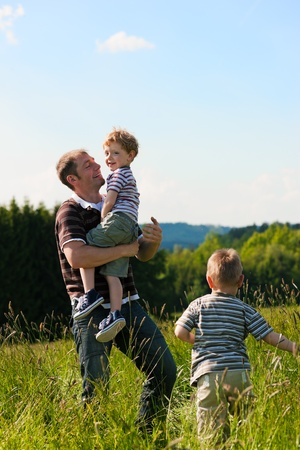 father and son: Father with two little boys playing in the grass on a summer meadow carrying one of the kids