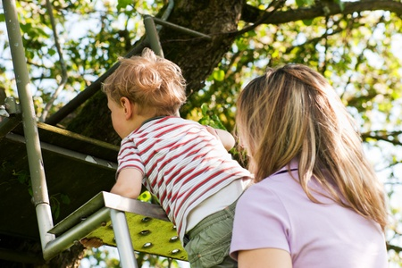 Little boy and his mother climbing up a ladder, they want to reach their tree house (house not to be seen) photo