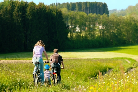 weekend activities: Family with boy child having a weekend excursion on their bikes on a summer day in beautiful landscape