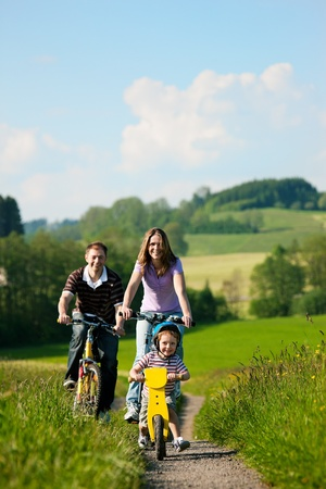 family activities: Family with boy child having a weekend excursion on their bikes on a summer day in beautiful landscape