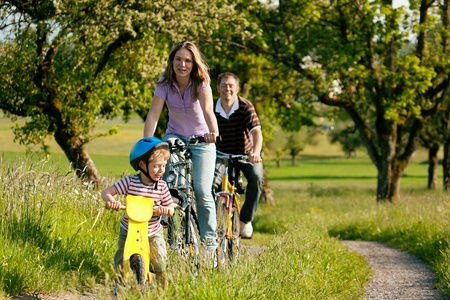Family with boy child having a weekend excursion on their bikes on a summer day in beautiful landscape photo