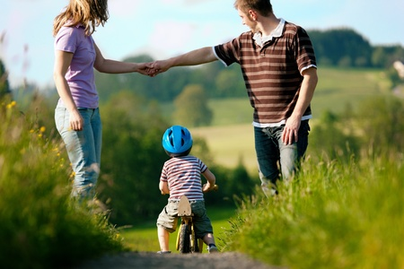 Family with boy child having a weekend excursion, the parents are walking while the son practices on a training bike photo